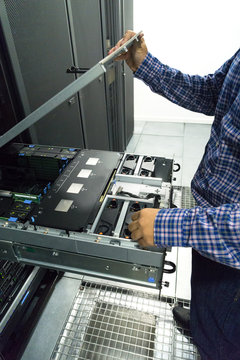 Technician opening the top of a server in a server room