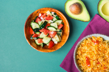 Traditional National Mexican Tomato Rice Stewed Pilaf with Hot Chili Peppers Garlic in Turquoise Bowl. Fresh Cucumber Onion Salsa Salad Avocado for Guacamole. Green Background. Top View. Copy Space