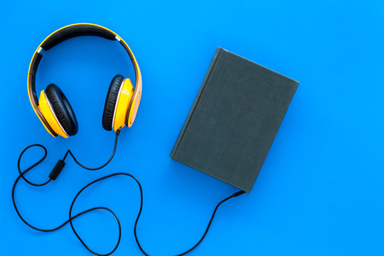 Audiobooks concept. Headphones connected with hardback book with empty cover on blue background top view copy space