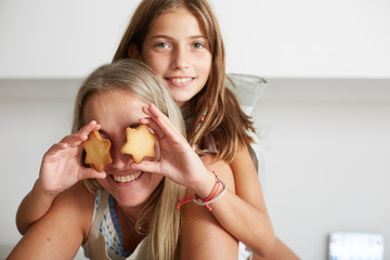 Mother and daughter looking at camera in a funny mood playing with christmas cookies