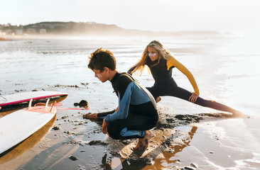 Two teenage friends doing stretching before surfing