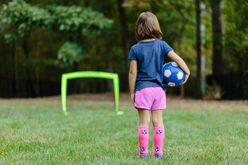 Young girl looking towards a practice goal with a soccer ball under her arm