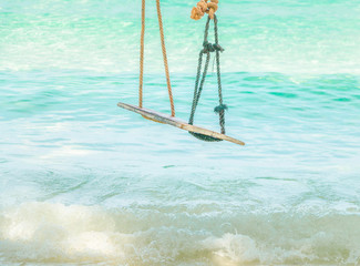 Wooden swing hanging on a branch of tree at the turquoise sea, Thailand.Exotic tropical paradise swings over crystal blue ocean sea with kayak landscape.