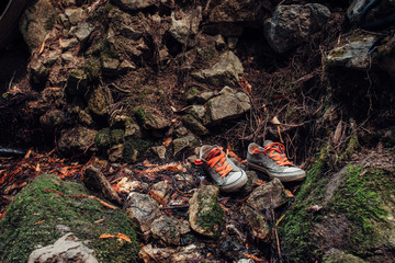 Pair of shoes on wet rocks in a forest