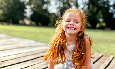 Portrait of a smiling little redhead girl