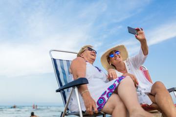 Senior women having fun at the beach taking a selfie