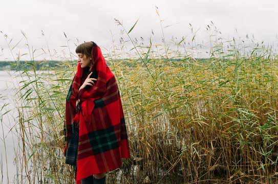Portrait of young woman covered with  bright wooden plaid