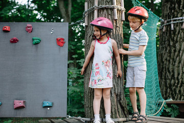 Boy and girl in helmets standing near the artificial boulder in the rope course park