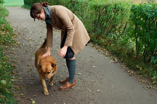 Young woman stroking homeless dog