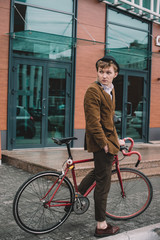 Young stylish guy with bicycle