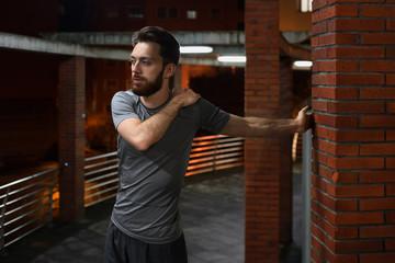 Man warming up at brick column