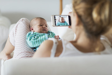 Mother taking picture of her newborn baby
