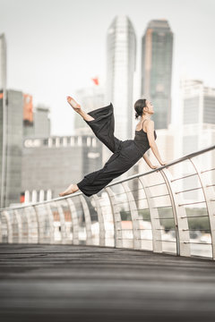 Cute Young woman athlete performs a perfect straddle leap high up, with perfect control while smiling, on a bridge  with background of skyscrapers