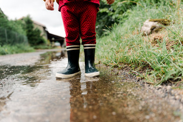 toddler rain boots int a puddle