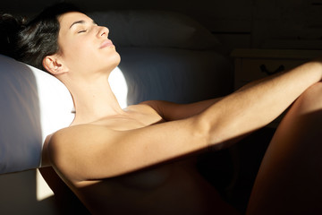 Naked woman relaxing at bed in sunlight on her face and neck.
