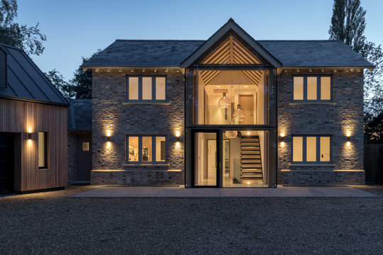 Modern glass fronted house illuminated at night.