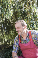 Senior man in red apron laughing outdoors