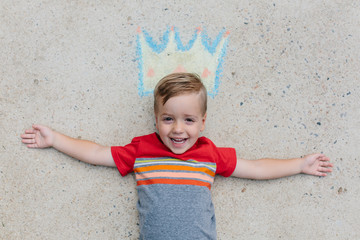 Cute happy boy laying on the ground wearing a crown drawn in chalk