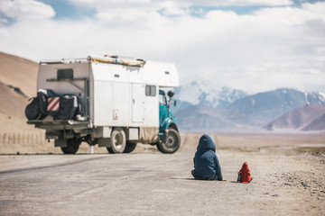 young boy and his red parrot sitting on a road on the pamir high beside a camping truck