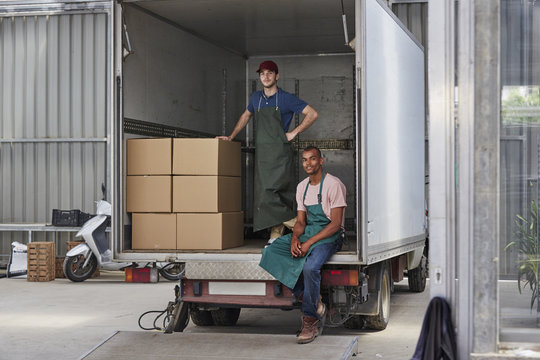 Confident Workers In Truck With Cardboard Boxes Outside Greenhouse