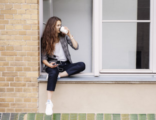 Young woman drinking a coffee while sitting in a window.
