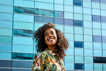 Pretty businesswoman with afro smiling over glass building.
