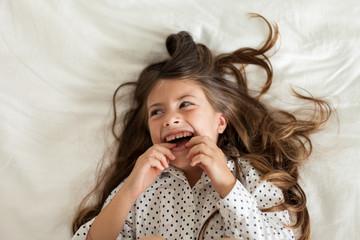 Laughing child wearing black and white polka dot shirt