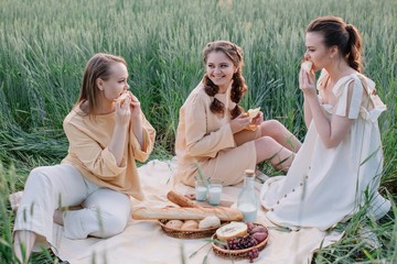 Tree lovely sisters eating melon and enjoying warm summer evening outdoors