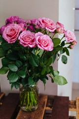 Indoors shot of bouquet of pink delicate roses in glass vase