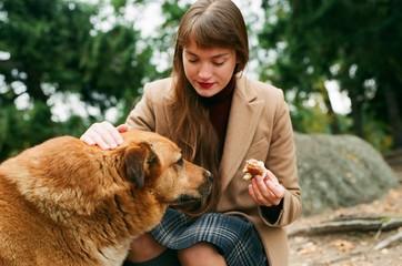 Girl sharing food with homeless dog