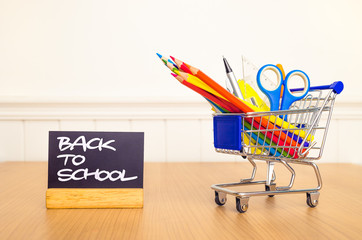 Shopping cart with school supply and back to school lettering on blackboard . white background