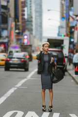 Young professional woman putting on headphones in the city