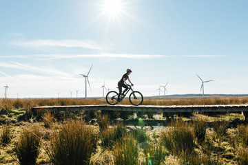 A woman riding a mountain bike in over a wooden track surrounded by wild grass at a wind farm in Scotland
