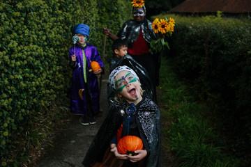 Four children in Halloween costumes walk together.