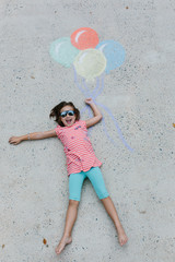 Young girl with sunglasses holding on to balloons drawn on the ground