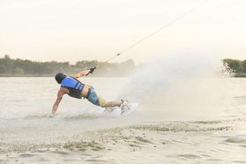 Man splashing water while riding with wakeboard on the lake