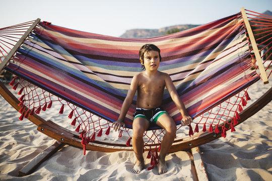 6 year old boy sitting on a hammock on the beach
