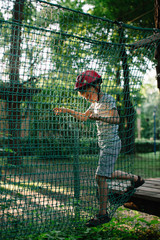 Adorable boy in helmet walking on rope course