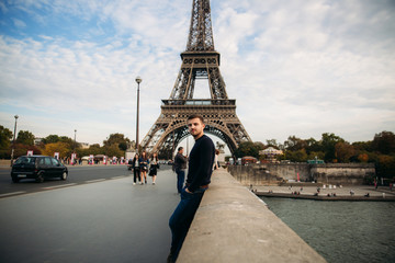 Handsome man in dark pullover is standing on the bridge background of the Eiffel Tower