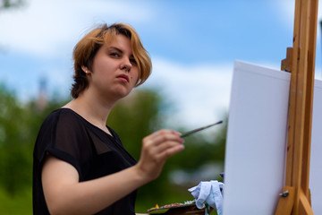Artist  young woman paints on a canvas an urban landscape of a summer of oil paints in city park