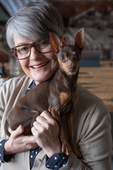 Portrait of mature woman holding small dog
