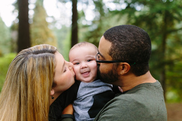 Parents Kissing Baby's Cheeks