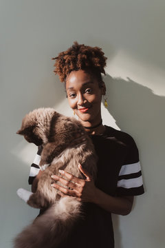 An african american woman at home playing with her cat