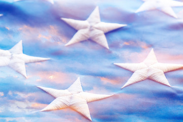 Combined image of close-up of white stars embroidered on US flag and sunset sky