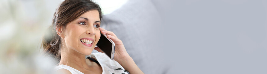 Young cheerful woman in couch talking on mobile phone, template
