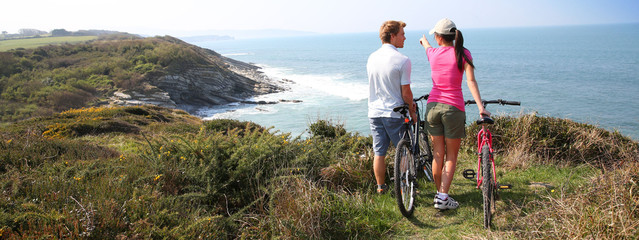 Couple on biking day stopping by coastline, template