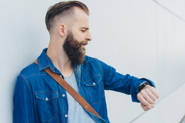 Young bearded man looking at his watch