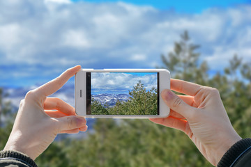 Girl holding phone and taking photo of nature vally with two hands