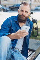 Young bearded man using mobile phone