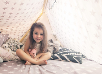 Cute happy little girl playing with toys and dreaming in teepee and bed.